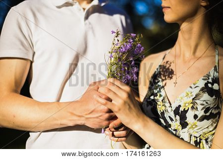 Loving couple in the forest on a sunny day. To love each other. Silhouettes of people Conceptual photo. A man and woman hold each other's hands. Wild flowers in hands