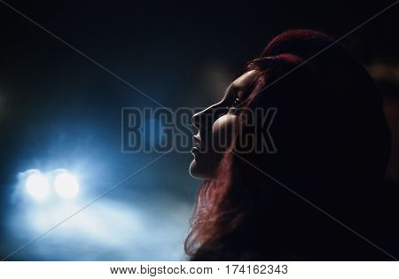 Redhead girl in a red beret standing on night street. Light from the car on the woman's face. Beautiful face profile. The dark night street
