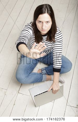pretty girl put her hand forward and hiding laptop notebook stopping this gesture annoying photographer