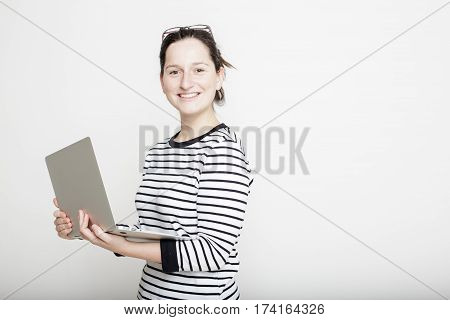 Beautiful young female student with glasses stands proudly smiling and holding a notebook in her hands