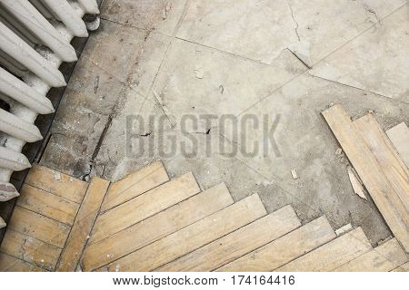 Old rotten parquet floor is partially dismantled.