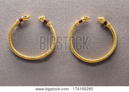 Couple of ancient braided gold bracelets with dragon heads as ornaments on a fabric background