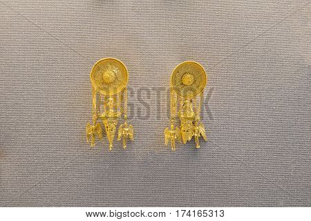 Pair of golden earrings made in ancient greece showing Eros holding a iynx and couple of female winged Nike