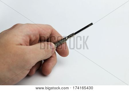 Hand holds an hour-long screwdriver on white background.