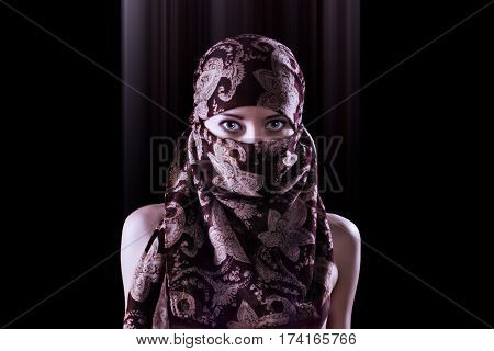 Surreal portrait of a mysterious oriental style woman in hijab with piercing eyes. Stylized and toned image