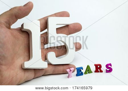 Hand holds a number fifteen on a white background.