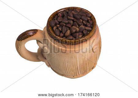 Decorative ceramic mug with pine nuts isolated on white background.
