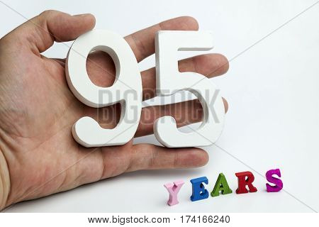 Hand holds a number ninety-five on a white background.