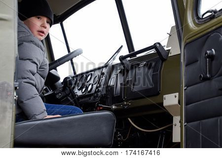 The Child Sits In The Cabin Air Defense Missile System. Exhibition Equipment At An Air Show.