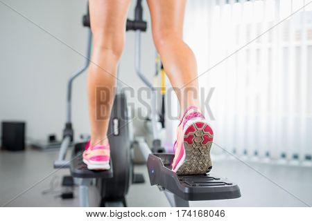 Young woman's muscular legs on stepper/treadmill, closeup