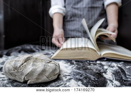Baker chef looking for a recipe in a cookbook in the foreground is piece of dough on the black wooden table covered with flour