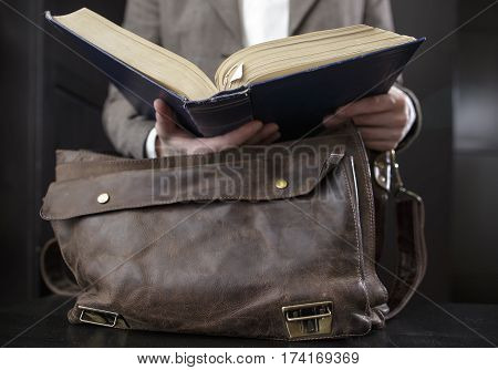 teacher in a jacket gets a book from an old leather briefcase standing on a table in the audience and opened