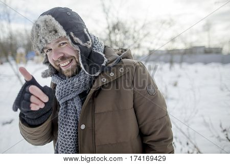 smiling man shows and explains the index finger in the winter outdoors in a fur hat and jacket