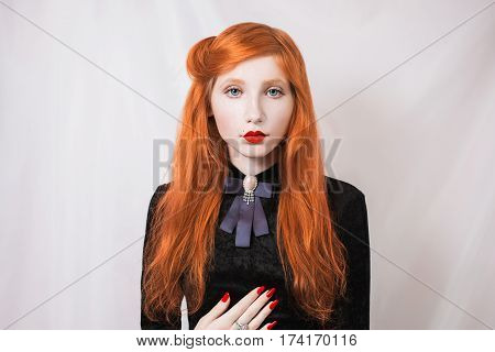 Woman with red straight hair wearing a black dress on a white background. Red-haired girl with pale skin and blue eyes and a bright unusual appearance with a ring on her finger and red nails