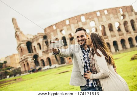 Young Couple Taking Selfie In Front Of Colosseum In Rome, Italy