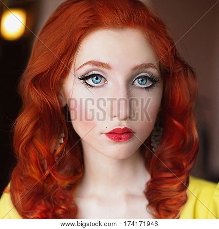 A woman with red hair in yellow dress. Red-haired girl with pale skin blue eyes a bright unusual appearance red lips and false eyelashes