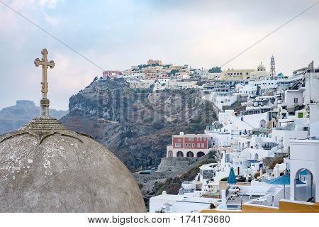view of fira town and cross on dome of church on Santorini