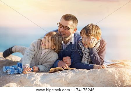 Father reading a book to his children outdoors