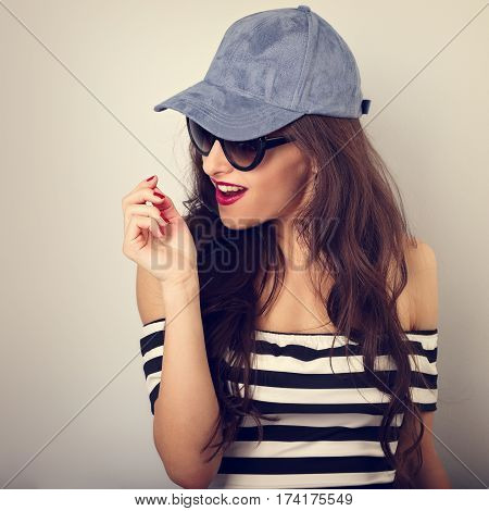 Happy Enjoyment Young Woman In Sunglasses And Blue Baseball Cap Posing In Striped Blouse. Closeup Ha