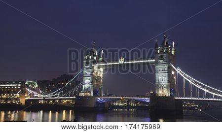 Tower Bridge with reflections in the thames river at night in London, United Kingdom, England