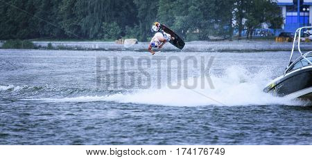 A wakeboarder in the air. Performs a pirouette jump. White foam on the water. The visible part of the boat.
