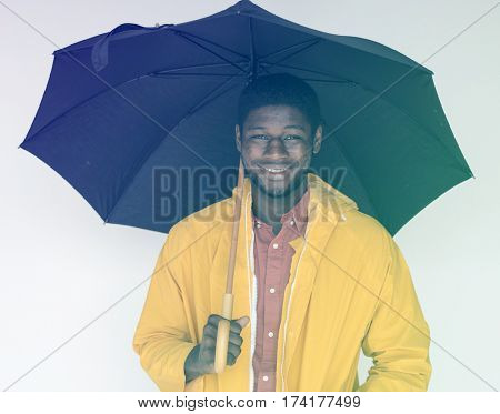 African man with umbrella and raincoat on white background
