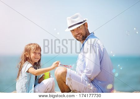 Happy father with his daughter making soap bubbles during summer vacation