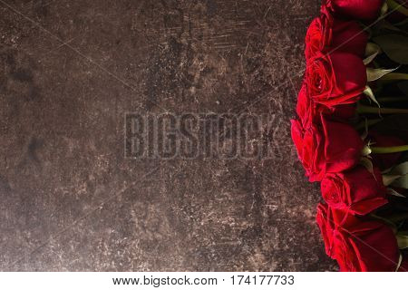 Roses flowers lie on a dark marble table. Big beautiful bouquet of red roses flowers. Texture colors. A flowers gift for a wedding birthday Valentine's Day. Space for text and design. Flat lay flowers copyspace. Flowers on dark table