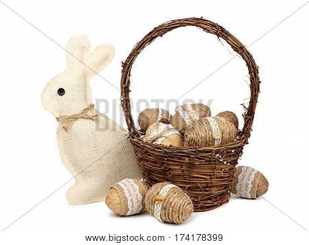 Rustic Easter Eggs In A Basket With Burlap Bunny Isolated On A White Background