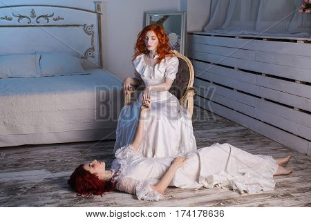Two beautiful girls with red hair in a beautiful white wedding Victorian dresses. Female style. The fragile girl. Thin waist. A woman sits on a chair. Conceptual photography. Girl lies on the floor