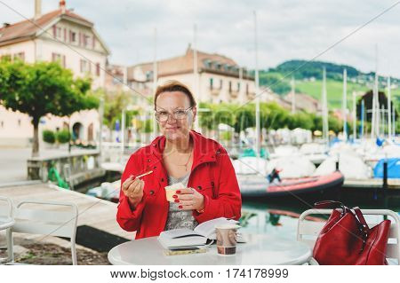 50-60 year old woman resting outdoors, reading book in cafe by lake Geneva, Switzerland