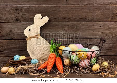 Easter Scene With Bunny, Twine Carrots And Basket Of Eggs Against A Rustic Wood Background
