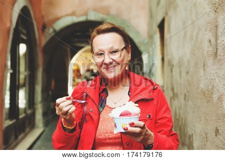 50-60 year old woman eating ice cream outdoors