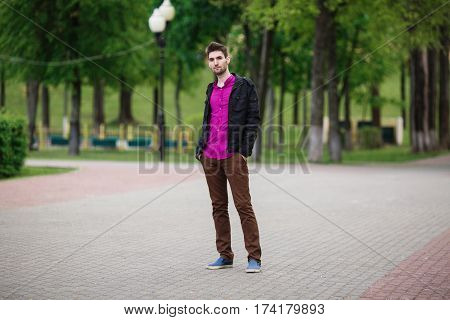Young attractive cheerful man with dark hair with a beard wearing a shirt and a black jacket on the street. Male street style. Nature in spring. Walking around the city.
