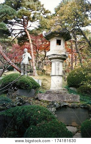 An ancient stone lantern in a garden at the Narita-san Shinshō-ji Shingon Buddhist temple in Narita, Japan.
