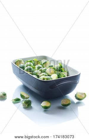 raw Brussels sprouts in ceramic form on a wooden table