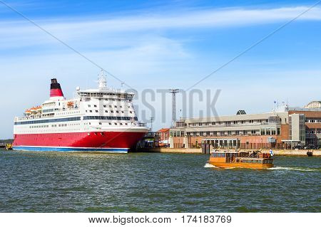 Cargo-passenger cruise ferry moored in Bay at pier in Helsinki port. Waiting for passengers boarding from terminal. Wooden motor boats with tourists navigate in South Harbour Gulf. Suomi Helsingfors