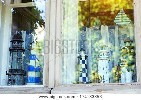 Decorative handmade figurines nautical lighthouses stand at window behind glass. Homemade Souvenirs marine theme in Nordic port city. Scandinavia Suomi Helsingfors Suomenlinna