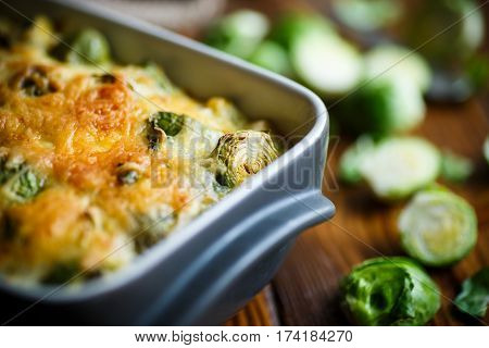 Brussels sprouts baked in sauce with cheese in a ceramic form