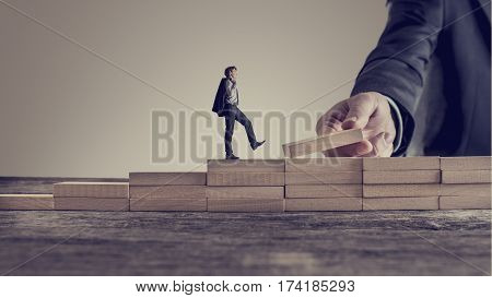 Retro vintage style image of a business person walking up steps while the hand of other man building stairs for him in a conceptual image of personal and career promotion leadership and opportunity.