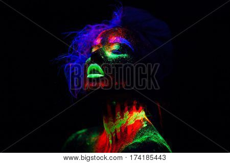 Beautiful extraterrestrial model woman in neon light. It is portrait of beautiful model with fluorescent make-up, Art design of female posing in UV with colorful make up. Isolated on black background
