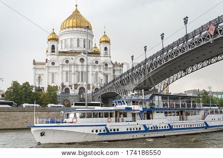 Pleasure boat on the Moscow river passes under the bridge.