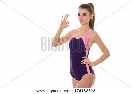 beautiful slender girl in a body suit keeps his hand on the side and it shows gesture second hand isolated on white background