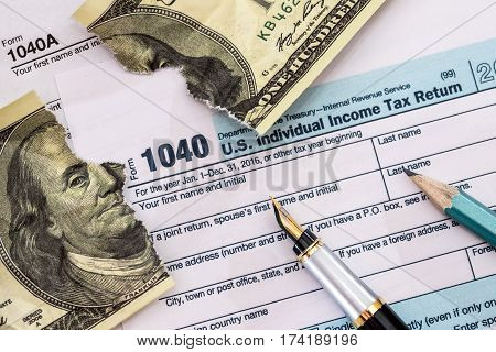 Torn Dollar On Usa 1040 Tax Form On Desk.