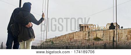 Young couple take picture with a mobile the Acropolis in Athens.