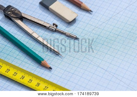 Pencil, Compass And Rulers On Graph Paper Background