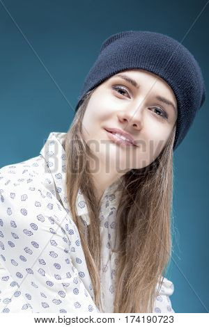 Portrait of Smiling Young Caucasian Girl Holding Black Hat Posing Against Green Background. Vertical Image Orientation