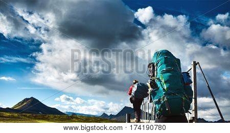 two hikers on the trail in the Islandic mountains. Trek in National Park Landmannalaugar, Iceland. valley is covered with volcano asher