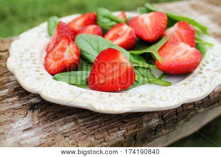 Fresh spinach salad with strawberries on a wooden background