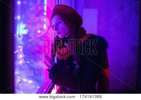 A woman with red curly hair braided in a braid in a black coat a scarf around his neck and a red beret looking out the window with a blue light. Red-haired girl with bright unusual appearance.